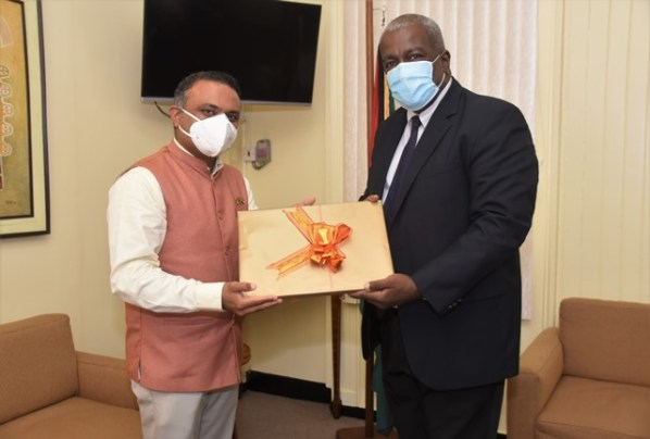 Prime Minister, Hon, (R'etd) Brigadier Hon. Mark Phillips receives a token of appreciation from High Commissioner of India to Guyana, H.E. Dr. K. J. Srinivasa when he paid him a courtesy call at the Office of the Prime Minister this morning