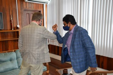 Attorney General and Minister of Legal Affairs, Hon. Mohabir Anil Nandlall, and the British High Commissioner, H.E. Greg Quinn greet eachnother in keeping with the COIVD-19 health protocols