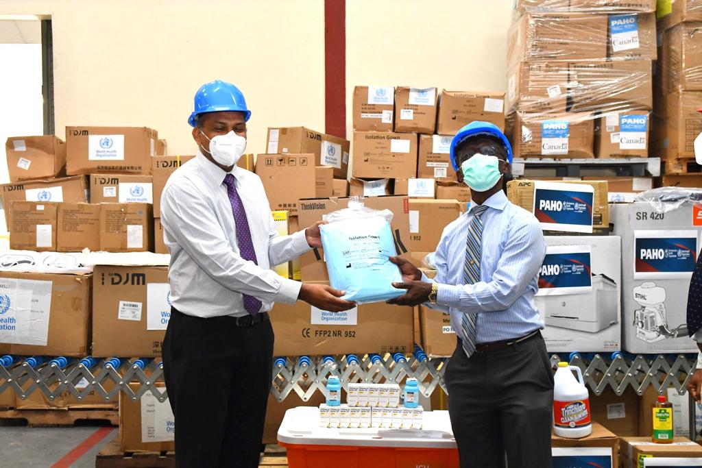 Minister of Health, Hon. Dr. Frank Anthony, receiving the protective equipment from the PAHO/WHO Representative, Dr. William Adu Krow