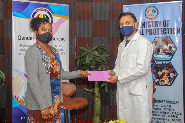 Shemika Henry received the cheque from representative of the Humanitarian Mission Guyana Incorporated, Dr. Suresh Sugrim