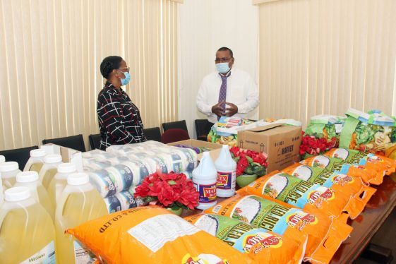 Permanent Secretary, Ministry of Human Services and Social Security, Ms. Lorene Baird, and Mr. Latchman Bharat, a representative of the Church of Jesus Christ of the Latter-Day Saints examine the hampers donated