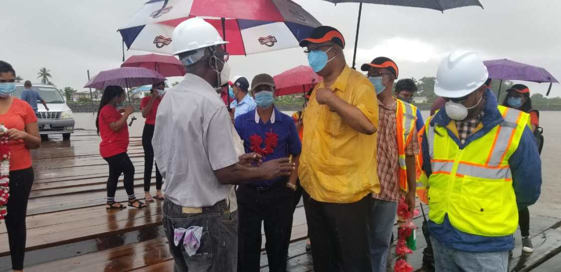 Minister of Public Works, Hon. Juan Edghill speaking to Aubrey Walcott, Site Engineer during an early morning inspection of the ongoing works at the Legaun Stelling, Region 3
