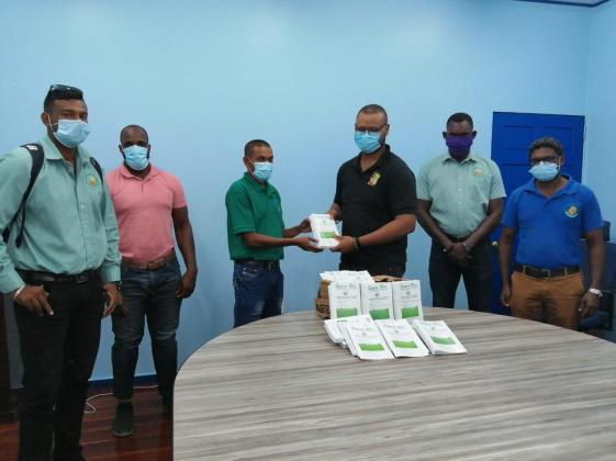 Communication Officer for the Guyana Rice Development Board presents a copy of the booklet to Extension Manager Mr. Bissessar Persaud