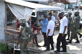Prime Minister Brigadier Mark Phillips interacts with residents on his way to visit the relatives of murdered teenagers, Masters Isaiah and Joel Henry.