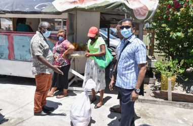 Minister of Public Affairs within the Office of the Prime Minister, Mr. Kwame McCoy (left) gestures as he interacts with a recipient of a hamper, during a distribution exercise held in Kingston, Georgetown today. Councillor of the City of Georgetown, Mr. Bishram Kuppen is also pictured first, right