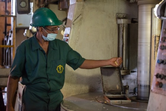 An employee of the Uitvlugt-Wales estate examines finished product after cane is processed into sugar.