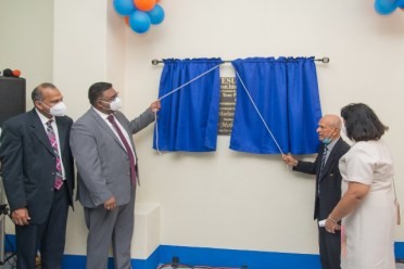 President Dr. Mohamed Irfaan Ali and Dr. Yesu Persaud unveiling the plaque as Minister of Health, Hon. Dr. Frank Anthony looks on