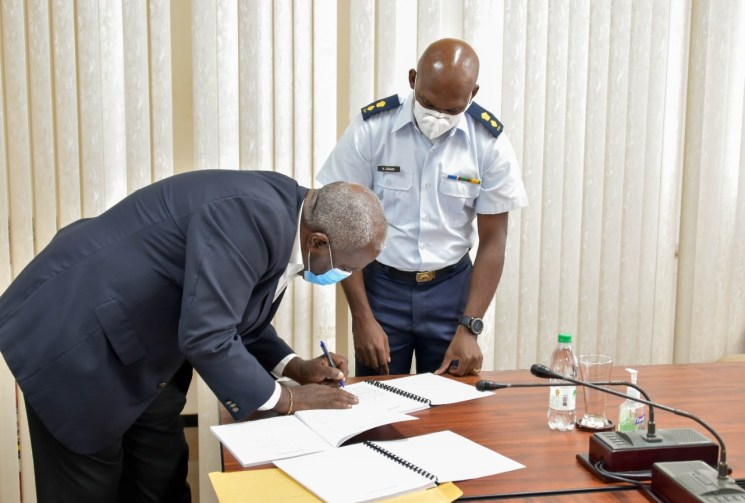 Prime Minister, Brigadier Mark Phillips (left) affixes his signature to a copy of the National Oil Spill Contingency Plan, as the Director-General of the Civil Defence Commission (CDC), Lieutenant Colonel Kester Craig pays keen attention
