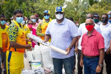 President Dr. Mohamed Irfaan Ali presents a quantity of cricket gear to this Wakenaam cricket team