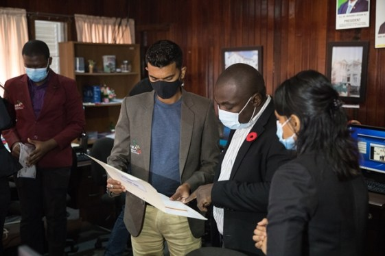Minister of Public Affairs within the Office of the Prime Minister, Hon. Kwame McCoy and GNBA staff peruse a document.