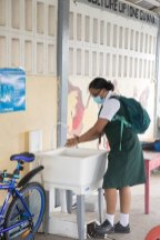 This student washes her hands at West Demerara Secondary School