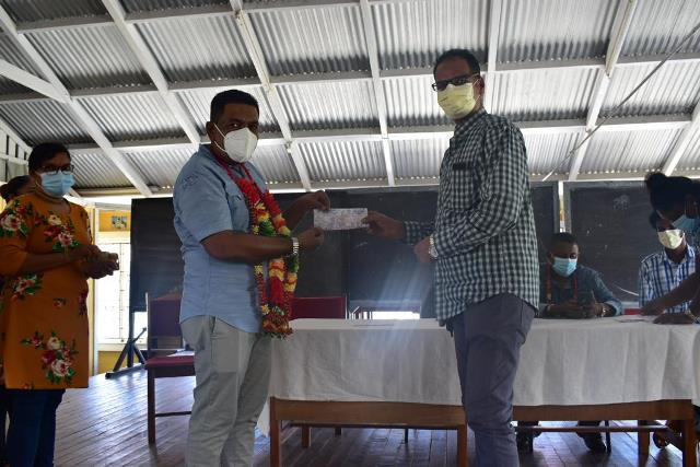 Minister of Agriculture, Hon. Zulfikar Mustapha hands over uniform and school supplies voucher to a parent in Region Six