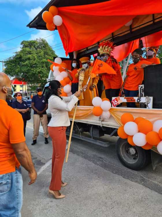 Ms. Mae Toussaint Jr. Thomas, Permanent Secretary at the Minister of Home Affairs receives the baton and an orange flag