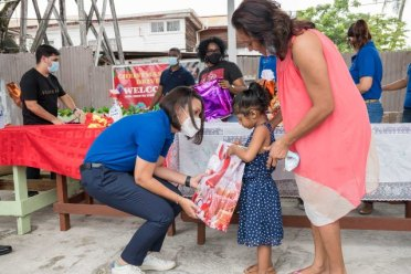 Minister of Housing and Water, Hon. Susan Rodrigues distributing toys to the littles one of Albouystown Community