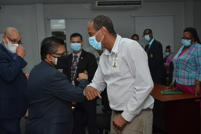 Minister Singh greets a senior staff of the GRA today