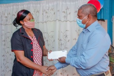 Principal Education Officer, Mr. Immanuel Bridgewater handing over vouchers to Head Teacher of St. Stephen's Primary School, Ms. Wendy Johnson