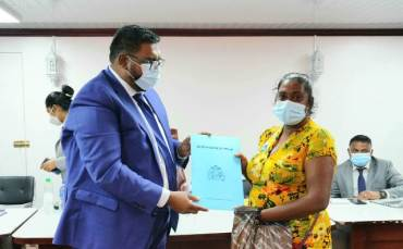 President Ali presents Pratima Devi Sookdeo with her certificate of title