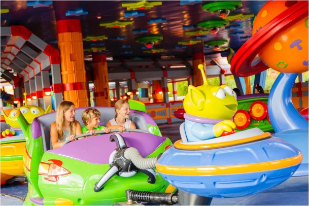 """Little green Aliens from Pixar Animation Studios' Toy Story films pilot toy rocket ships in the Alien Swirling Saucers attraction in Toy Story Land at Disney's Hollywood Studios. The out-of-this-world attraction is inspired by Andy's toy playset from the Pizza Planet restaurant. With multi-colored lighting and sound effects from throughout the galaxies, Walt Disney World guests swirl and whirl in the toy rocket ships while the Aliens try to get captured by """"The Claw"""" that hangs overhead. (Steven Diaz, photographer)"""