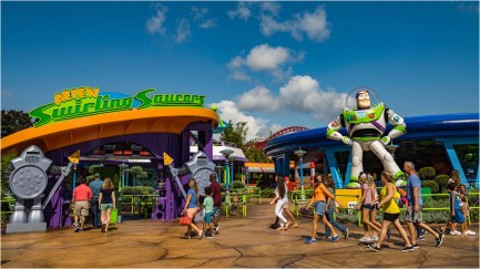 """Little green Aliens from Pixar Animation Studios' Toy Story films pilot toy rocket ships in the Alien Swirling Saucers attraction in Toy Story Land at Disney's Hollywood Studios. The out-of-this-world attraction is inspired by Andy's toy playset from the Pizza Planet restaurant. With multi-colored lighting and sound effects from throughout the galaxies, Walt Disney World guests swirl and whirl in the toy rocket ships while the Aliens try to get captured by """"The Claw"""" that hangs overhead. (Matt Stroshane, photographer)"""