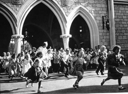 OPENING DAY, FANTASYLAND (1955) -Ð Hundreds of children run through Sleeping Beauty Castle after the long-awaited lowering of the drawbridge into Fantasyland.