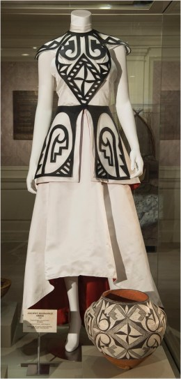 """Fashion designer Loren Aragon (Acoma Pueblo) used the patterns on a jar (bottom right) made in the 1900s by an Acoma Pueblo potter as inspiration for this """"Ancient Resonance"""" dress. The jar is on loan from the Museum of Indian Arts and Culture. The items are currently on display in the gallery exhibition """"Creating Tradition: Innovation and Change in American Indian Art"""" in The American Adventure pavilion at Epcot. The Walt Disney World exhibition displays the work of contemporary Native artists alongside artifacts from centuries past, demonstrating how ancestral craftsmanship influences modern generations. (David Roark, photographer)"""