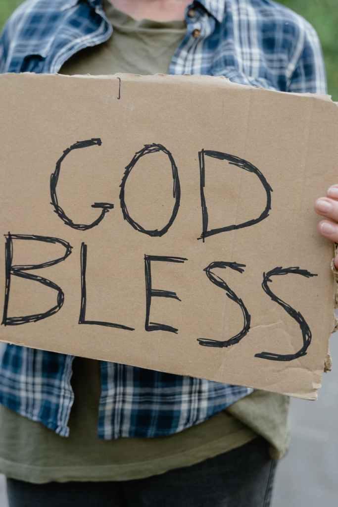 a man holding a god bless sign written on a cardboard