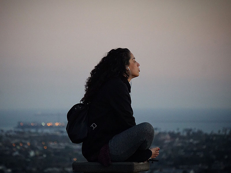 A woman listening to music and songs with these break up lyrics on a hill at sunset as she thinks about where she is.