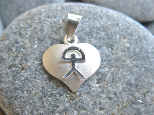 Close-up of heart pendant with matt silver background and shiny Indalo figure