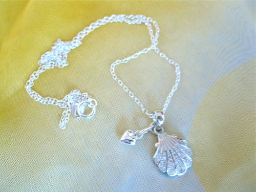 This gorgeous scallop shell with heart hangs on a sterling silver trace chain