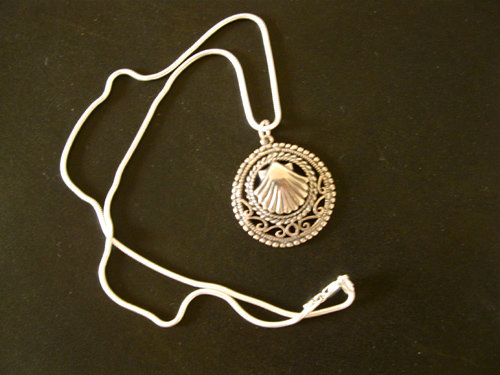 The scallop shell pendant hangs on a sterling silver snake chain