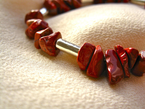 Red jasper chips and silver-coated ceramic tube beads make up this eye-catching bracelet