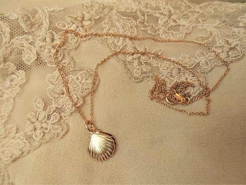 """The scallop shells hang on an 18"""" gold-filled chain"""