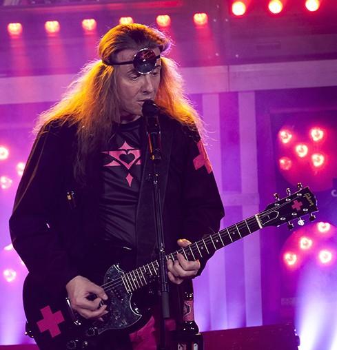 Ein Mann steht mit Gitarre auf einer Bühne