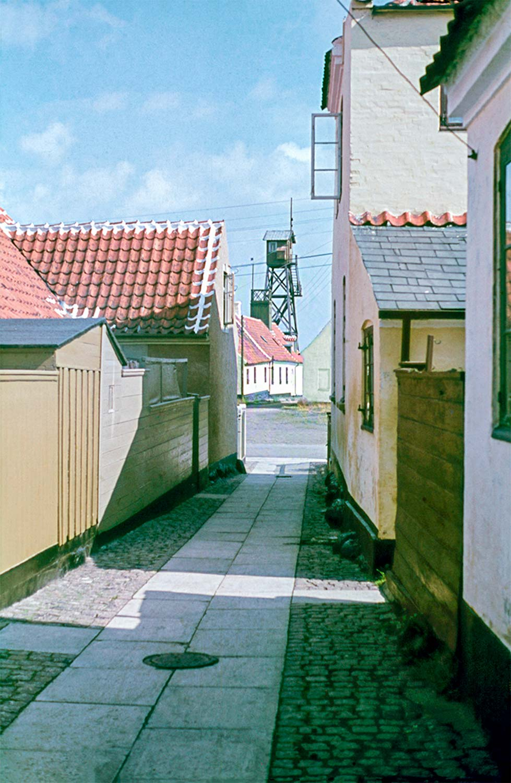 Kampensgade set mod øst med lodshuset og lodstårnet i baggrunden. I venstre side ses et udhus til Kampensgade 2 og Kampensgade 4. Til højre anes lidt af Strandstræde 6. Med åbent vindue ligger Kampensgade 3. 1944. Foto: Bertel Møller – Historisk Arkiv Dragør.