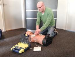Jesper Beck fra StrandEngs Hjerteløbergruppe demonstrerer brugen af en hjertestarter.