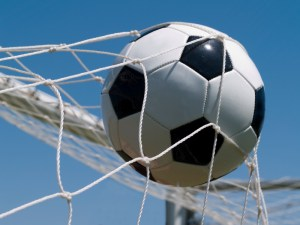 Soccer ball going into a goal