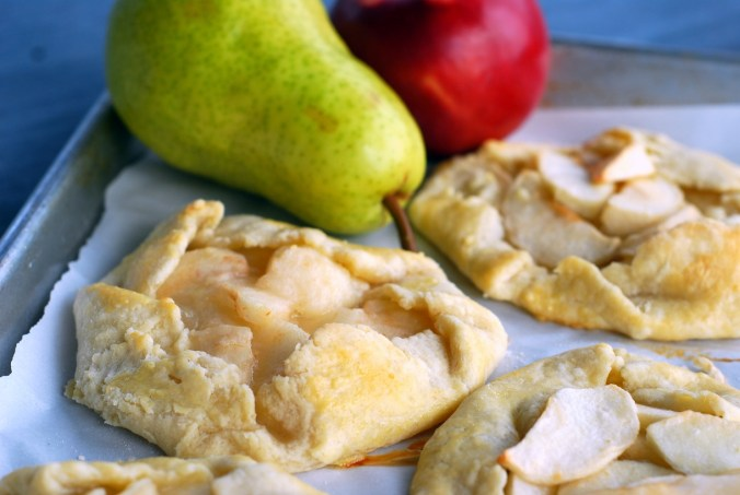 apple and pear galettes on baking sheet with fruit