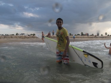 Mithun Madushanka, a surf trainer in training, surveys the waves with his longboard
