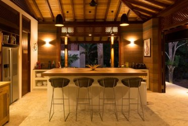 The use of rammed earth, with its ''ant farm'' colored layers, lends warm red, rust and brown hues to the kitchen interior. – Credit: Shehan Obeysekara