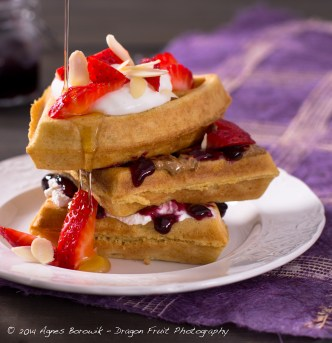 Triple decker Wheat-free waffles with almond butter, no sugar added jam, with fresh strawberries, goat milk yogurt, and almond slivers with a drizzle of pure maple syrup.