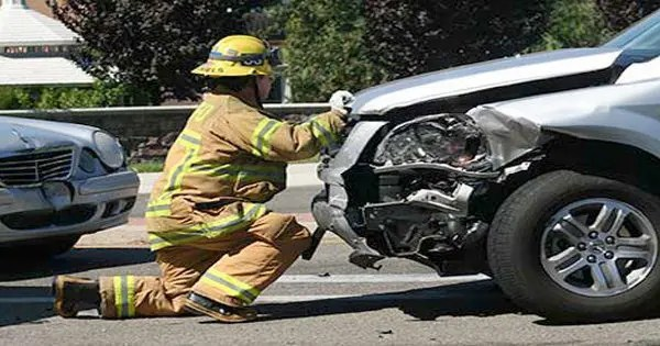 blog picture of firefighter at auto accident looking at front of car