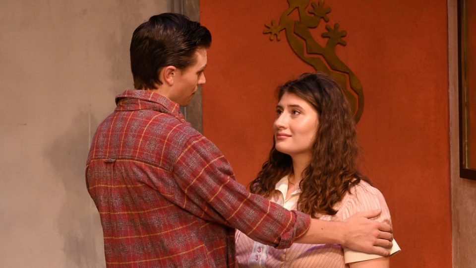 "SDA Student Antoinette Ricchio photographed performing in the play ""When You Comin' Back, Red Ryder?"", she is wearing a red and white blouse top, and looking directly at her co-star as he is embracing her by holding her shoulders."