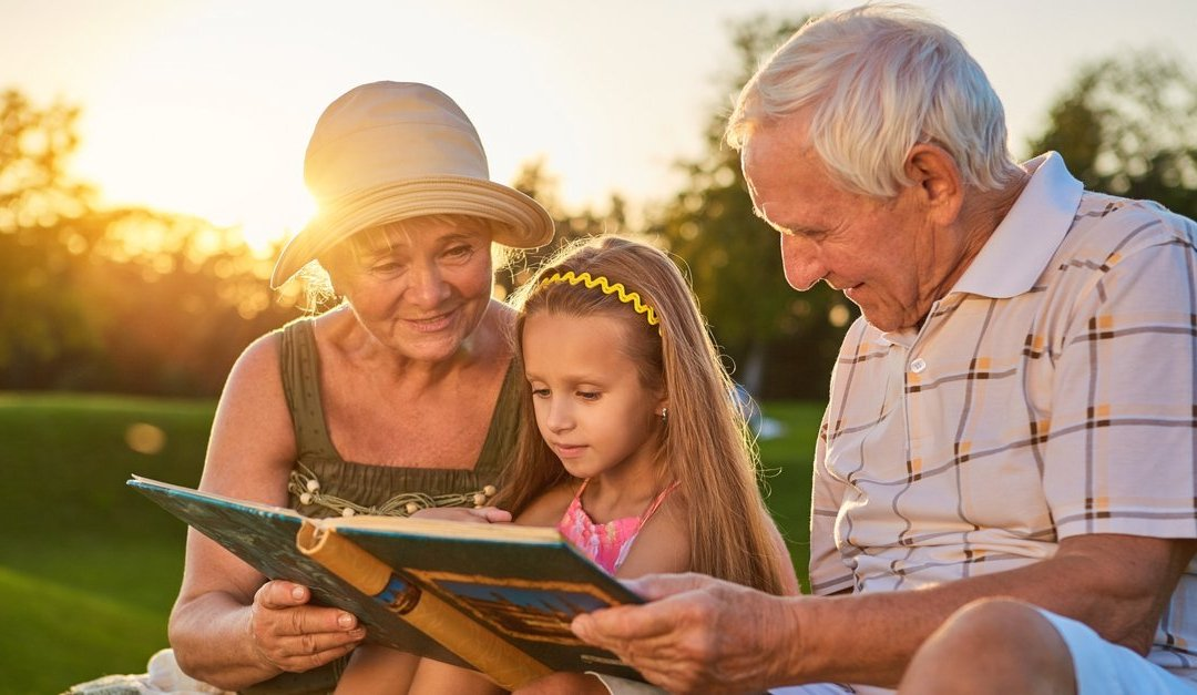 Image of grandparents reading to granddaughter
