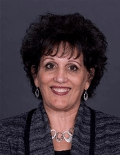 A smiling woman with dark hair and a grey suit stands in front of a greu background.