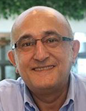 A man wearing an open-necked shirt and glasses smiles for the camera.