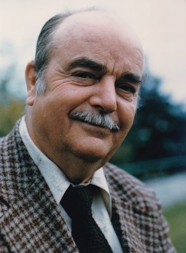 Smiling older man with salt and pepper receding hair, a moustache and laughing eyes. He wears a checked sportsjacker and tie.