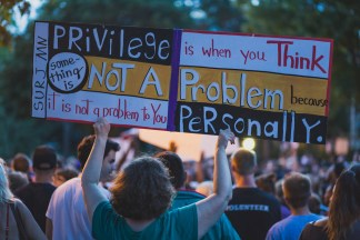 "someone holding a sign reading ""privilege is when you think something is not a problem because it is not a problem to you personally"""