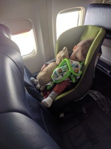 toddler asleep in car seat by the window