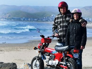 Zufallsbegegnung am Strand: Ron Cook mit seiner Freundin und ihrer Honda Dax – der Mann, der beim Rekord- versuch auf dem El-Mirage-Salzsee 1997 einen Horrorcrash überlebt hat