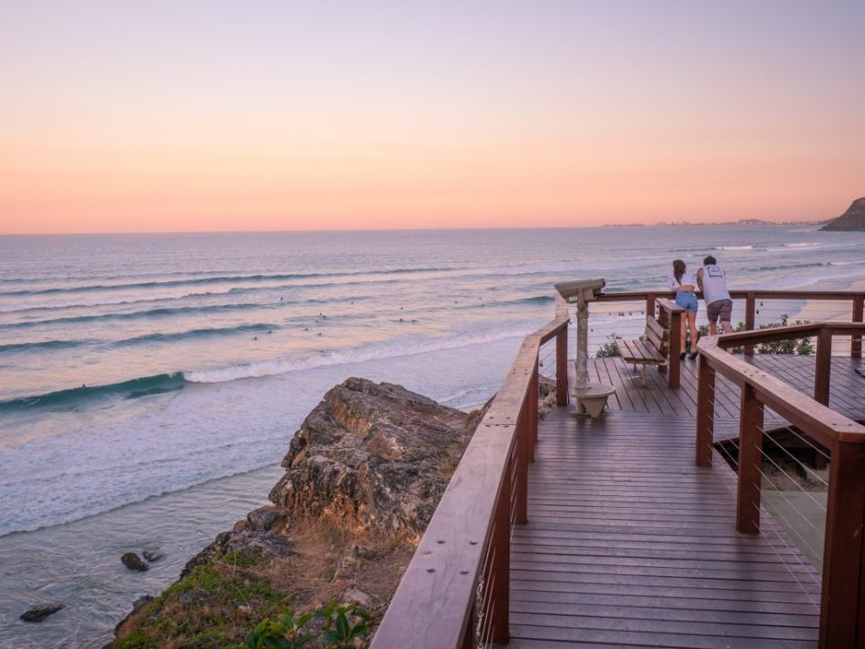 Two people looking out into the ocean overlooking Burleigh with pastel coloured sunset.